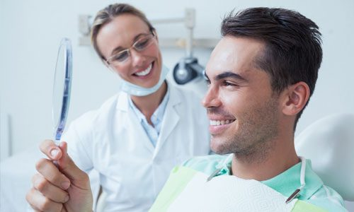 man admiring teeth - New Patient Info on Dental Insurance