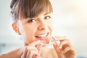 Woman putting in Invisalign clear aligners